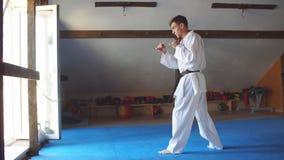 Hombre en el kimono blanco con karate del entrenamiento de la correa negra en gimnasio metrajes