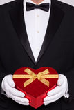 Hombre en el lazo negro que sostiene un rectángulo en forma de corazón de chocolates Foto de archivo libre de regalías