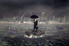 Hombre en el mar con la ciudad y el hundimiento griego de la bandera Fotografía de archivo