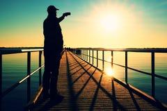 Hombre en el mar de la mañana de la fotografía del embarcadero Turista con el teléfono elegante a disposición Mañana fantástica Imágenes de archivo libres de regalías
