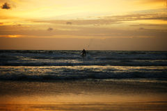 Hombre en el montar a caballo de la vespa en puesta del sol Imagen de archivo libre de regalías
