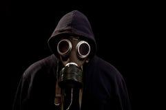 Hombre en el negro que lleva un maskr del gas una parte posterior de la oscuridad Fotos de archivo libres de regalías