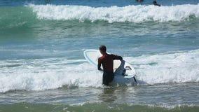 Hombre en el océano que entra del traje que practica surf, tablero que lleva en manos, deporte activo metrajes