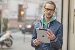 Hombre en el ordenador de la tablilla de Ipad del uso de la calle Imagen de archivo