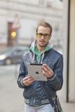 Hombre en el ordenador de la tablilla de Ipad del uso de la calle Fotos de archivo libres de regalías