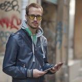 Hombre en el ordenador de la tablilla de Ipad del uso de la calle Imagenes de archivo