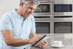 Hombre en el ordenador de la tablilla en café de consumición de la cocina Imagen de archivo libre de regalías