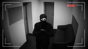 Hombre en el pasamontañas que corta la cámara CCTV en el edificio corporativo, pantalla gris del error almacen de video