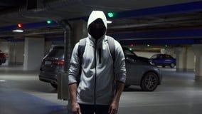 Hombre en el pasamontañas y la capilla en el estacionamiento subterráneo almacen de metraje de vídeo
