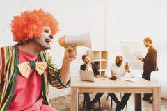 Hombre en el payaso Costume con el altavoz en oficina foto de archivo libre de regalías