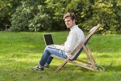 Hombre en el perfil que se sienta con el ordenador portátil en silla de jardín Fotografía de archivo