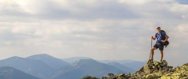 Hombre en el pico de la montaña Escena emocional Hombre joven con el backpac fotos de archivo libres de regalías