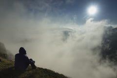 Hombre en el pico de montañas en la salida del sol - meditación fotos de archivo