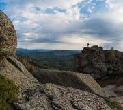Hombre en el pico en montañas Imagen de archivo libre de regalías