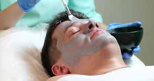 Hombre en el procedimiento del cosmético de la máscara metrajes