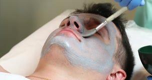 Hombre en el procedimiento del cosmético de la máscara almacen de video