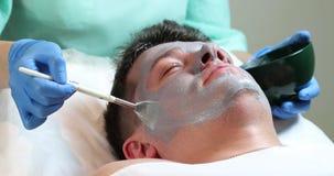 Hombre en el procedimiento del cosmético de la máscara almacen de metraje de vídeo