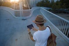 Hombre en el puente peatonal con la tableta Imagen de archivo