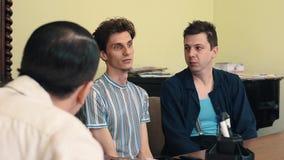 Hombre en el retroceso con el pie enojado de la red de pelo hacia fuera con dos visitantes en la reunión de la oficina almacen de video