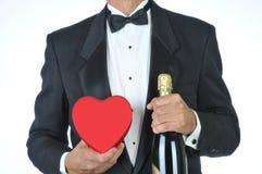 Hombre-en el smoking con el corazón y Champán rojos Foto de archivo libre de regalías