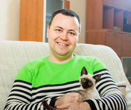 Hombre en el sofá   con el animal doméstico Imagenes de archivo