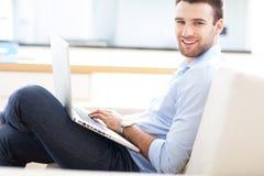 Hombre en el sofá con el ordenador portátil Imágenes de archivo libres de regalías
