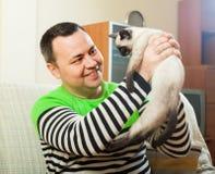 Hombre en el sofá con el pequeño animal doméstico Fotografía de archivo libre de regalías