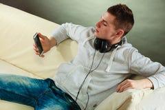 Hombre en el sofá con smartphone de los auriculares Foto de archivo