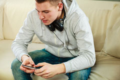 Hombre en el sofá con smartphone de los auriculares Imagen de archivo libre de regalías