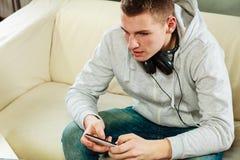 Hombre en el sofá con smartphone de los auriculares Fotos de archivo libres de regalías