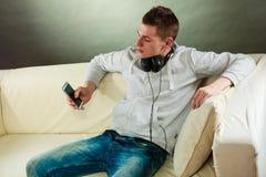 Hombre en el sofá con smartphone de los auriculares Fotografía de archivo