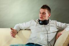 Hombre en el sofá con smartphone de los auriculares Imagen de archivo