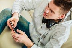 Hombre en el sofá con smartphone de los auriculares Imágenes de archivo libres de regalías