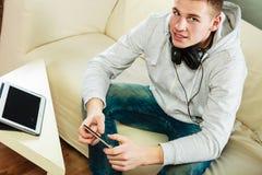 Hombre en el sofá con smartphone y la tableta de los auriculares Fotografía de archivo