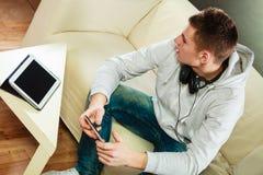 Hombre en el sofá con smartphone y la tableta de los auriculares Foto de archivo libre de regalías