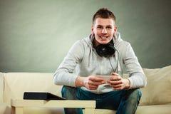 Hombre en el sofá con smartphone y la tableta de los auriculares Fotos de archivo