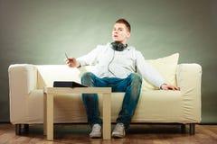 Hombre en el sofá con smartphone y la tableta de los auriculares Fotografía de archivo libre de regalías