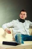 Hombre en el sofá con smartphone y la tableta de los auriculares Imágenes de archivo libres de regalías
