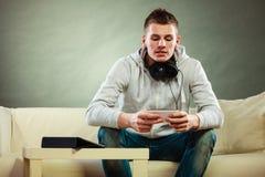 Hombre en el sofá con smartphone y la tableta de los auriculares Foto de archivo