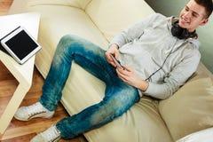 Hombre en el sofá con smartphone y la tableta de los auriculares Imagen de archivo