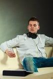 Hombre en el sofá con smartphone y la tableta de los auriculares Imagen de archivo libre de regalías