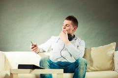 Hombre en el sofá con smartphone y la tableta de los auriculares Imagenes de archivo