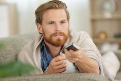 Hombre en el sofá cubierto con la manta usando teledirigido foto de archivo