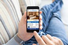 Hombre en el sofá que sostiene el teléfono con la pantalla de la reservación de hotel del app foto de archivo