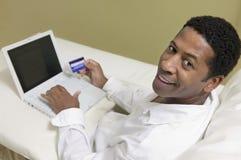 Hombre en el sofá usando la tarjeta de crédito para hacer la compra con la opinión de alto ángulo del retrato del ordenador portát Foto de archivo