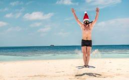 Hombre en el sombrero de santa en la playa tropical Fotografía de archivo