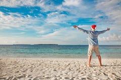 Hombre en el sombrero de santa en la playa tropical Imágenes de archivo libres de regalías