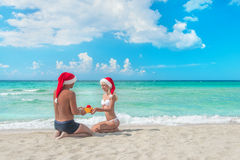 Hombre en el sombrero de santa que da un presente a su novia en el mar Foto de archivo libre de regalías