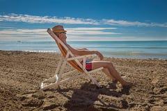 Hombre en el sombrero que se relaja en la playa, mirando el mar fotografía de archivo