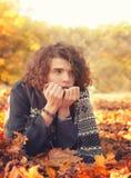 Hombre en el suéter de punto y la bufanda que mienten en las hojas de otoño, oudoor en parque del otoño Fotografía de archivo libre de regalías